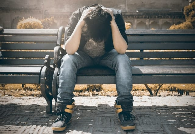 grief counseling - a man sitting on a bench grieving